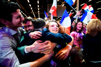 Supporters of French presidential election candidate Emmanuel Macron celebrate after the results of the first round of the presidential election, on April 23, 2017