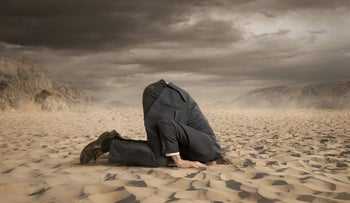 If I don't look, maybe stocks won't fall: Picture shows businessman in suit, on his hands and knees, with his head firmly rammed into the sand, ostrich-style. The sky is glowering.