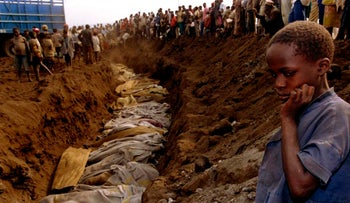 A Rwandan refugee girl stares at a mass grave where dozens of bodies have been laid to rest, July 20, 1994. Around 800,000 people were killed during the Rwandan genocide.