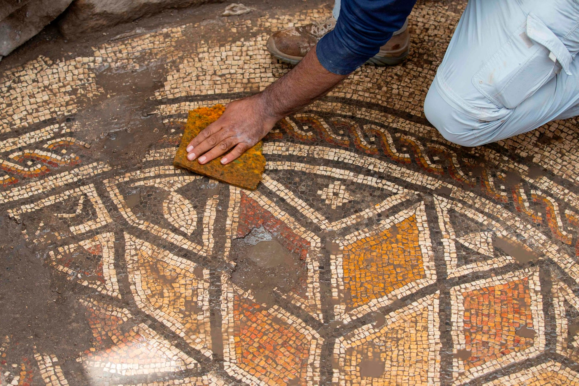 A worker cleans a mosaic floor during renovations at the ancient harbour of Caesarea on April 26, 2017, in the Israeli Mediterranean town.