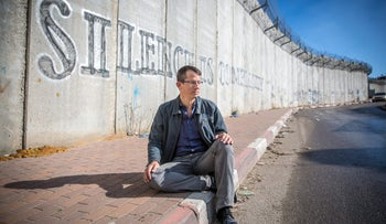 Will Israel's 'enemies' include its own business sector next? The picture shows Hagai El-Ad, head of B'tselem, sitting on the pavement by the wall separating Israel and the Palestinians. He is wearing glasses, a blue shirt, a differently blue jacket, grey trousers and black shoes.
