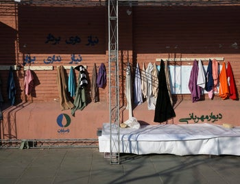 """Clothes hang on an outdoor charity wall with writing in Farsi at bottom right that reads, """"Wall of Kindness,"""" in downtown Tehran, January 7, 2016."""