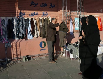 Iranian man puts clothes on hangers at an outdoor charity wall in downtown Tehran, January 7, 2016.