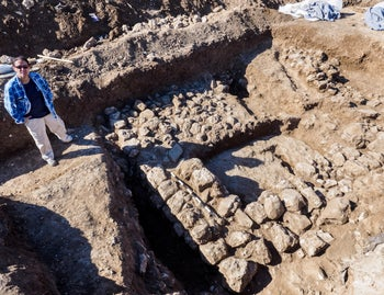 7,000-year old stone houses found in Jerusalem while building a road. Standing by the house wearing a plaid blue shirt over a dark blue T-shirt and trousers is Ronit Lupo, excavation director for the Israel Antiquities Authority.