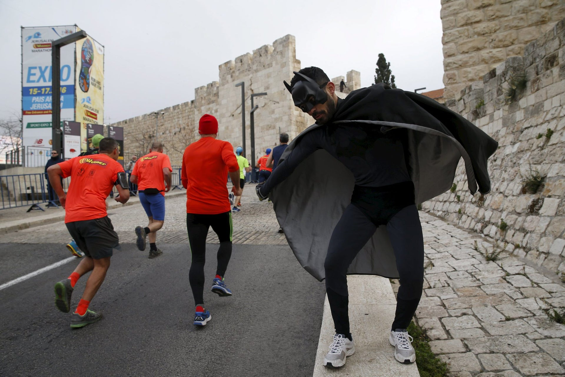 A man, dressed in a costume, encourages athletes running outside the Old City during the sixth international Jerusalem Marathon March 18, 2016.