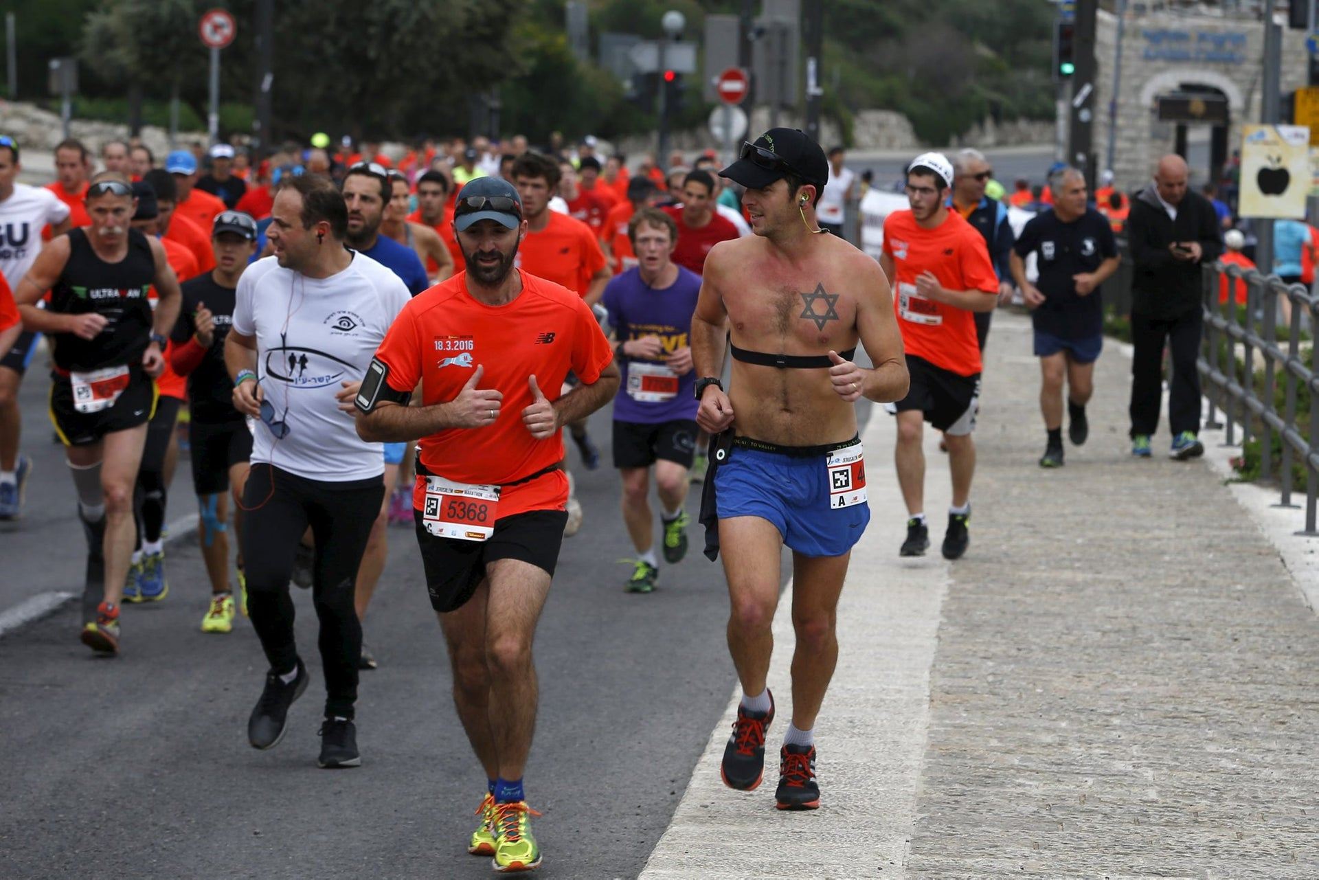 Athletes run outside Jerusalem's Old City as they participate in the sixth international Jerusalem Marathon, March 18, 2016.