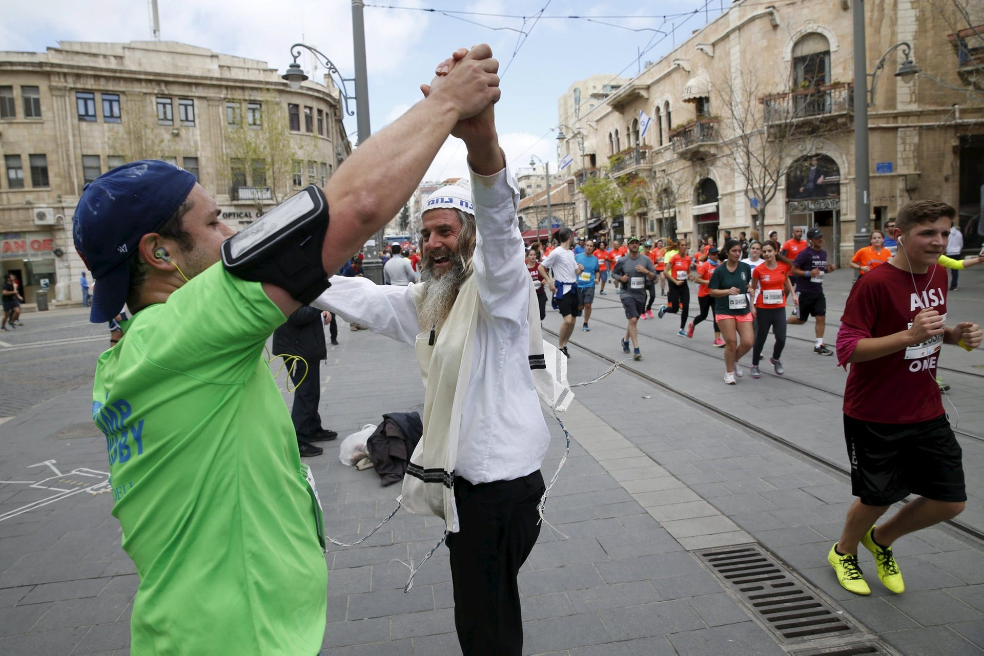 An ultra orthodox man dances with a participant of the sixth international Jerusalem Marathon, March 18, 2016.