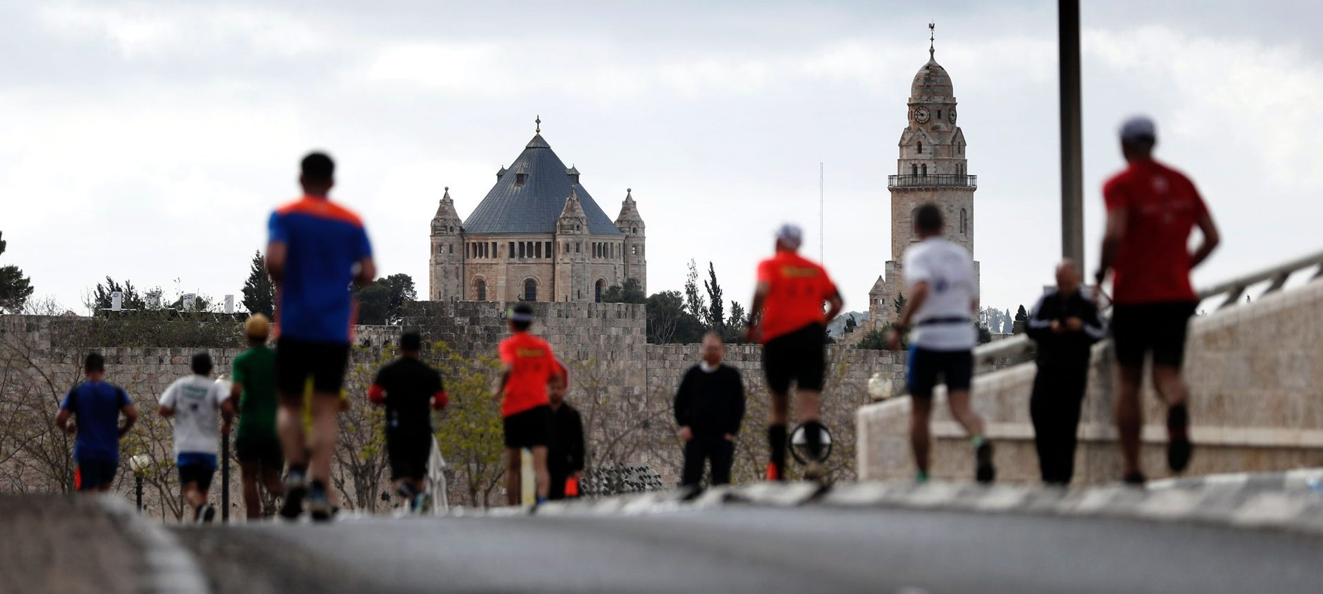 Competitors run towards Jerusalem's Old City with the Dormition Abbey (L) and the Nabi Daud mosque (R) on background during the 6th Jerusalem's marathon, on March 18, 2016.