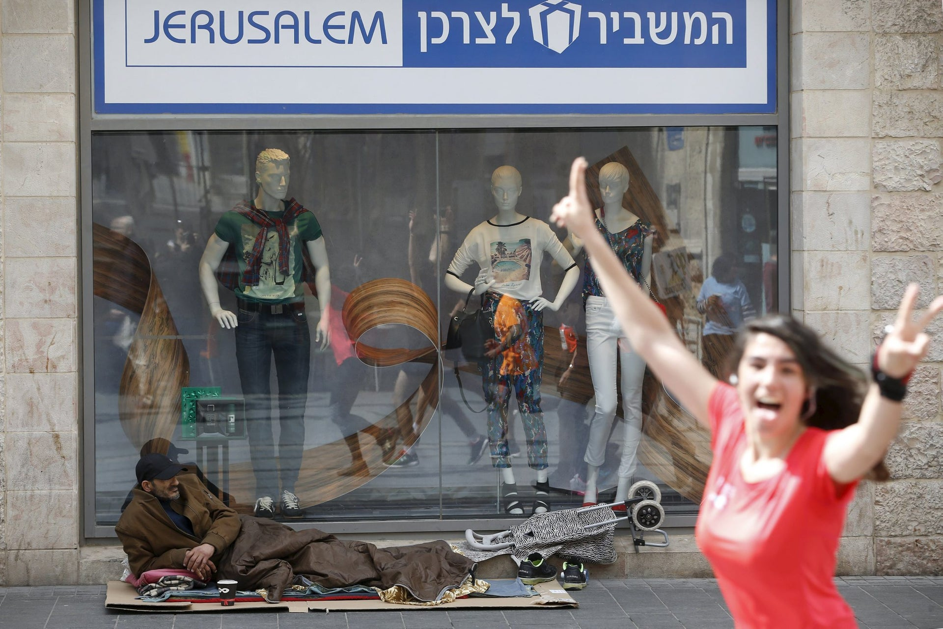 An woman gestures to the camera as a homeless man rests on the street during the sixth international Jerusalem Marathon, March 18, 2016.