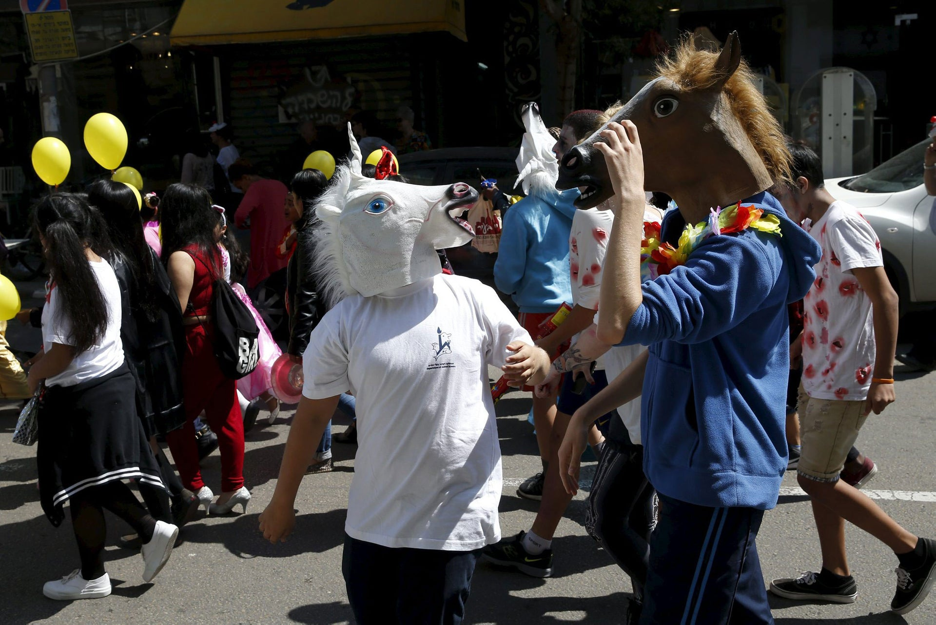 Children wear costumes as they take part in a parade marking the upcoming Jewish holiday of Purim outside the Bialik Rogozin school in Tel Aviv, Israel March 22, 2016.