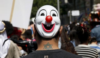 A man wearing a mask takes part in a parade marking the upcoming Jewish holiday of Purim outside the Bialik Rogozin school in Tel Aviv, Israel March 22, 2016.