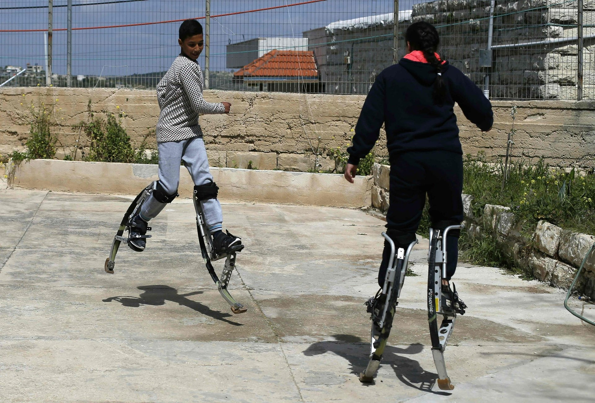 Young Palestinians train on long legs at the Palestinian Circus School in the village of Bir Zeit, near Ramallah on March 22, 2016.