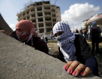 Female Palestinian protesters take cover during clashes with Israeli troops near Ramallah, October 10, 2015.