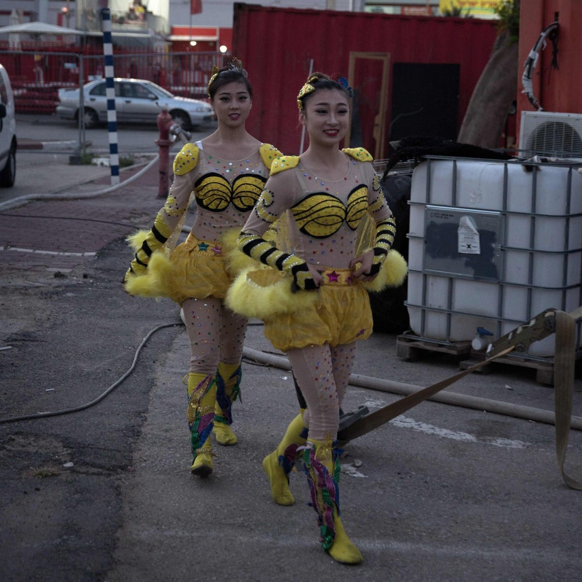 Chinese circus acrobats from the Hebei acrobatic troupe dressed up in costumes rush to get to the backstage area prior to their performance in the northern Israeli port city of Haifa on March 29, 2016.