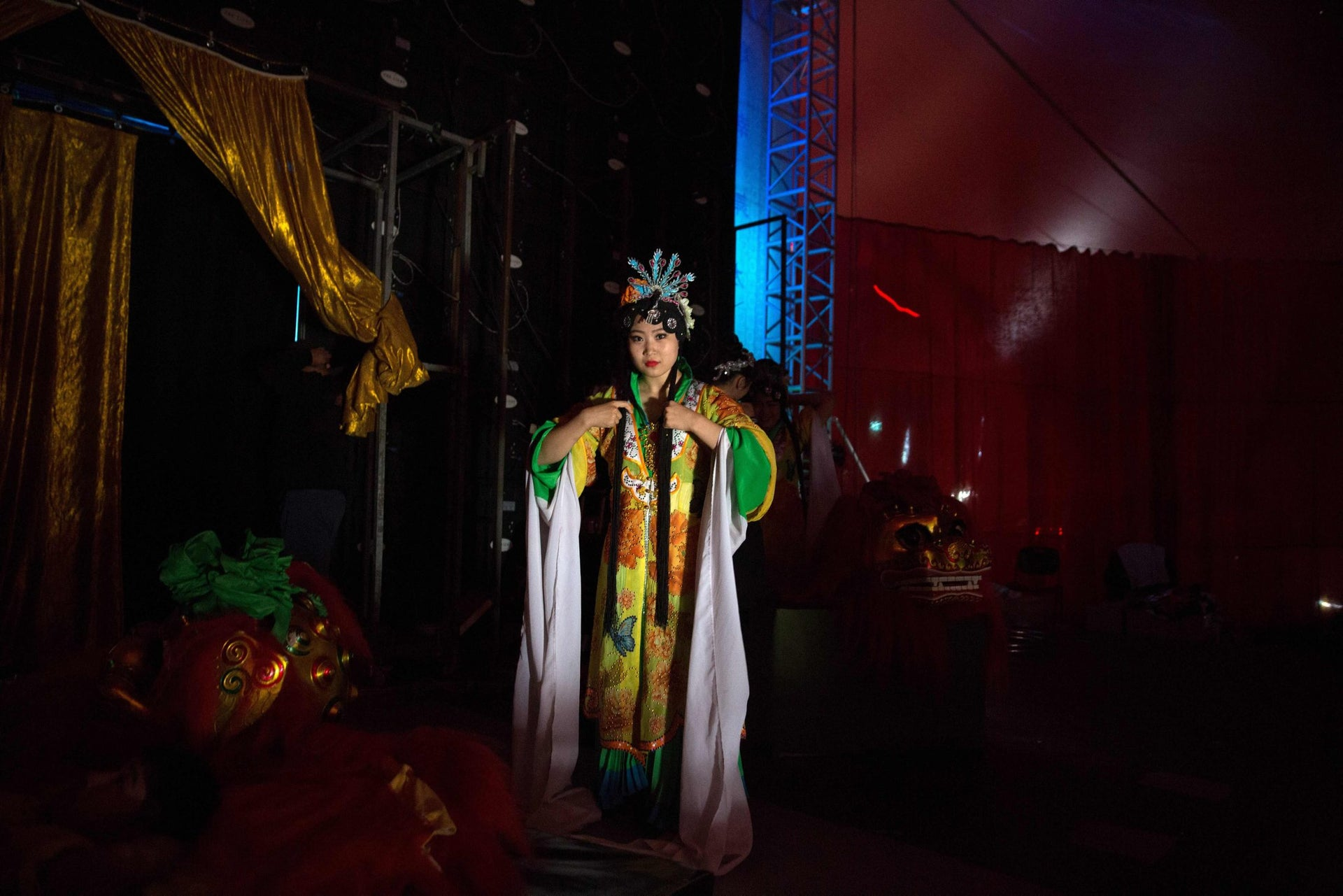 A Chinese circus acrobat from the Hebei acrobatic troupe puts on the final touches to her Chinese costume as she waits backstage prior to their performance in the northern Israeli port city of Haifa on March 29, 2016.