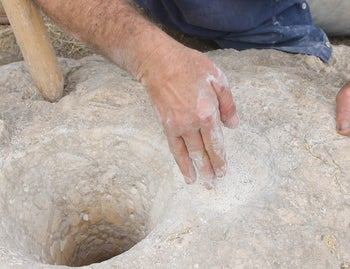 Prof. David Eitam demonstrates the removal of flour made from barley using 12,500-year old stone mortars found at Huruk Musa, a Natufian site in the Jordan Valley.