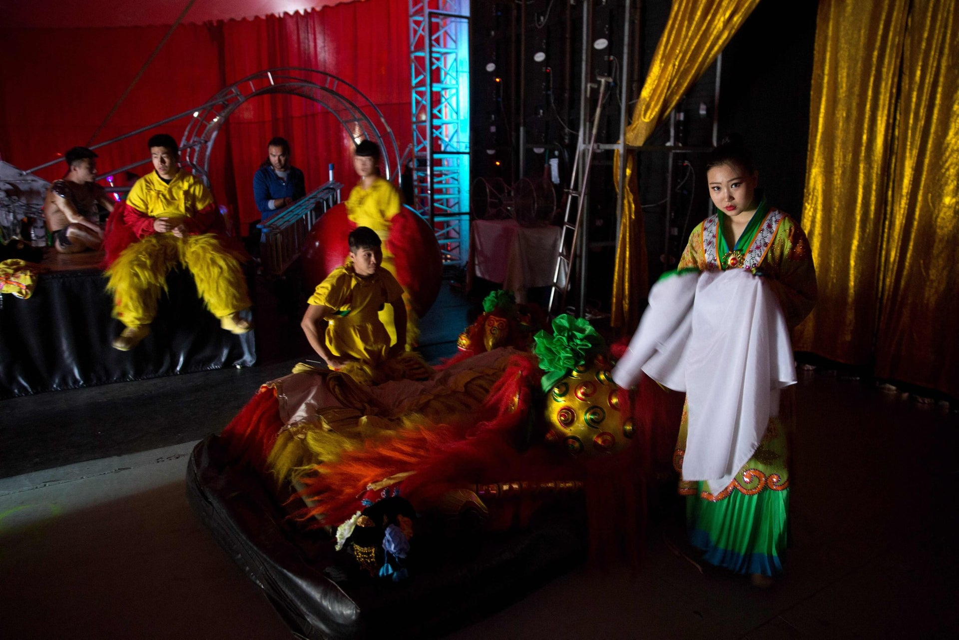 Chinese circus acrobats from the Hebei acrobatic troupe dressed up in costumes wait backstage prior to their performance in the northern Israeli port city of Haifa on March 29, 2016.