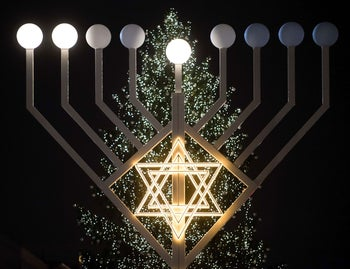 A giant eight- branched candelabrum Menorah is pictured in front of a Christmas tree during the holiday of the jewish religious festival of lights Hanukkah at the Brandenburg Gate in Berlin on December 7, 2015.