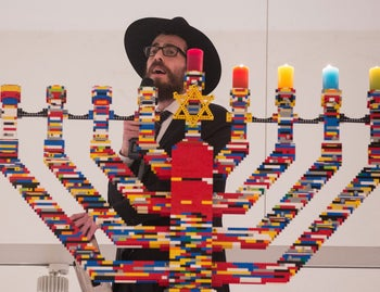 Rabbi Shmuel Havlin sings atop a ladder in front of Hanukkah candles made out of Lego blocks in the hall of the Joseph-Carlebach school in Hamburg, Germany, Dec. 9, 2015.