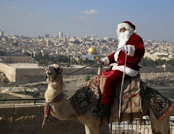 Israeli-Arab Issa Kassissieh wears a Santa Claus costume as he rides a camel and poses for the media during an annual Christmas tree distribution by the Jerusalem municipality on the Mount of Olives in Jerusalem. The Dome of the Rock is seen in the background. December 21, 2015.