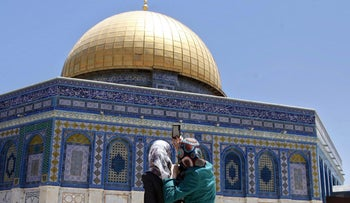 Palestinian women take a photo of Dome of the Rock Mosque in the Al Aqsa Mosque compound, on the third Friday of the Muslim holy month of Ramadan, in Jerusalem's old city, Friday, July 3, 2015.