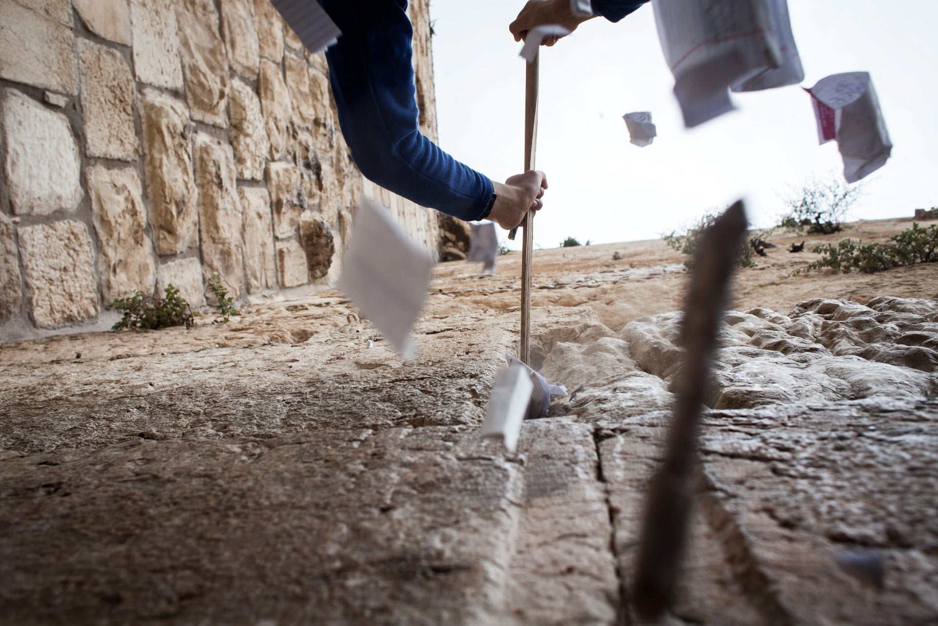 Prayer notes being cleaned out of the stones of the Western Wall in Jerusalem on April 12, 2016.