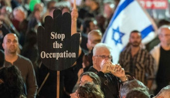 An Israeli woman holds up a poster during a rally to mark the 21th anniversary of the assassination of former Israeli Prime Minister Yitzhak Rabin at the Tel Aviv plaza where he was shot in the Mediterranean coastal city of Tel Aviv on November 5, 2016.
