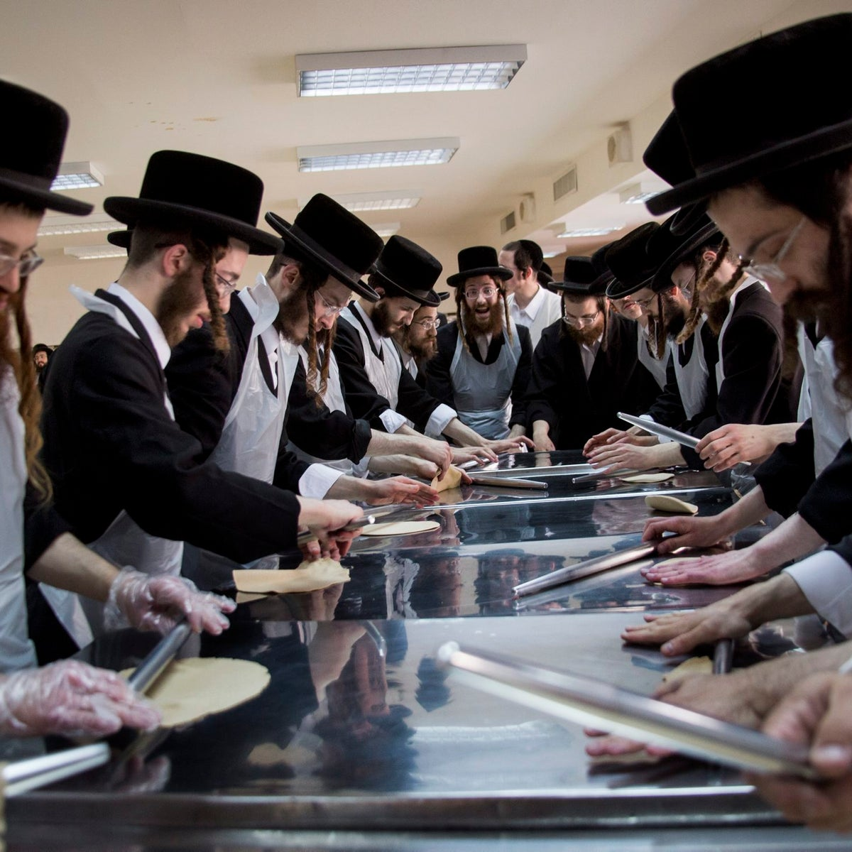 Ultra-Orthodox Jewish men knead the dough before baking Matzoth at a bakery in  Jerusalem, on April 13, 2016.
