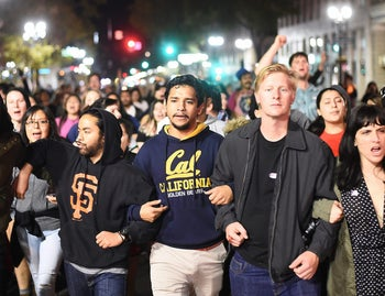Protesters against president-elect Donald Trump march peacefully through Oakland, California, U.S., November 9, 2016. A separate group earlier in the night set fire to garbage bins and smashed multiple windows.