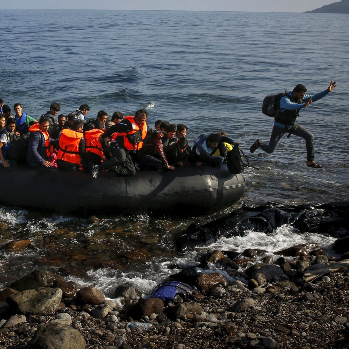 An Afghan migrant jumps off an overcrowded raft onto a beach at the Greek island of Lesbos, October 19, 2015.
