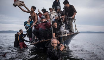 Migrants arrive by a Turkish boat near the village of Skala, on the Greek island of Lesbos, Nov. 1, 2015.