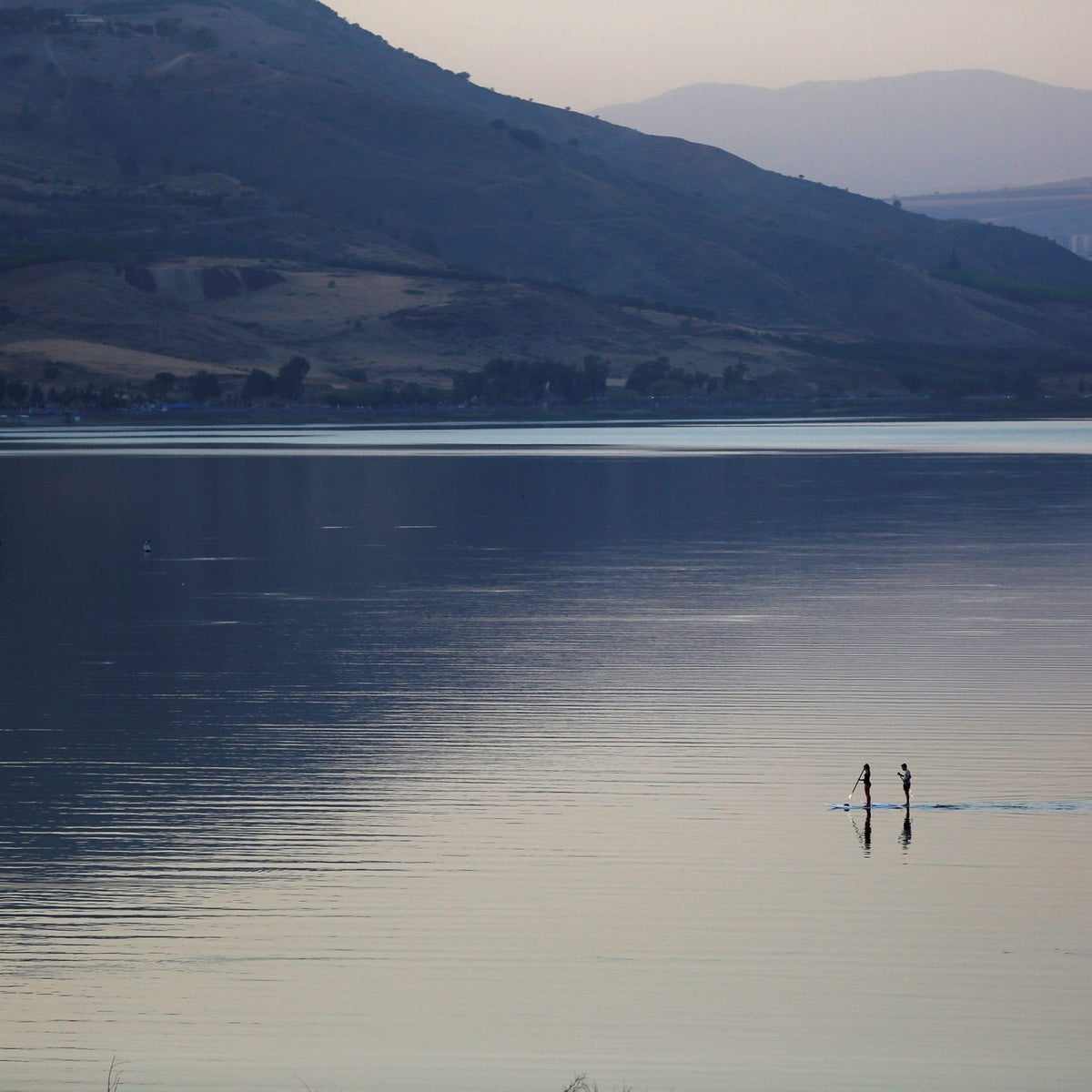 People paddle on a stand-up paddle board in the Sea of Galilee, northern Israel November 8, 2016.