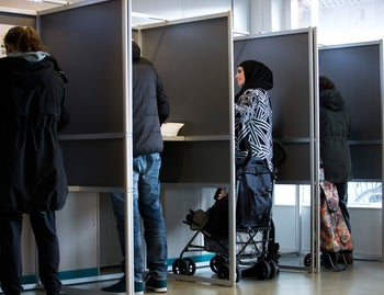 People fill out ballots prior to casting their votes for Dutch general elections in The Hague, Netherlands, Wednesday, March 15, 2017.