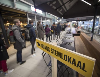 Commuters line up at a voting booth at Central Station in Utrecht to vote in Dutch general elections, March 15, 2017.