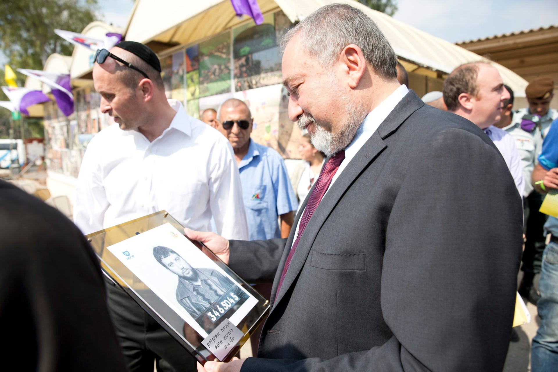 Defense Minister Avigdor Lieberman visits new IDF recruits, holding a photo of himself on the day he was drafted in the IDF.