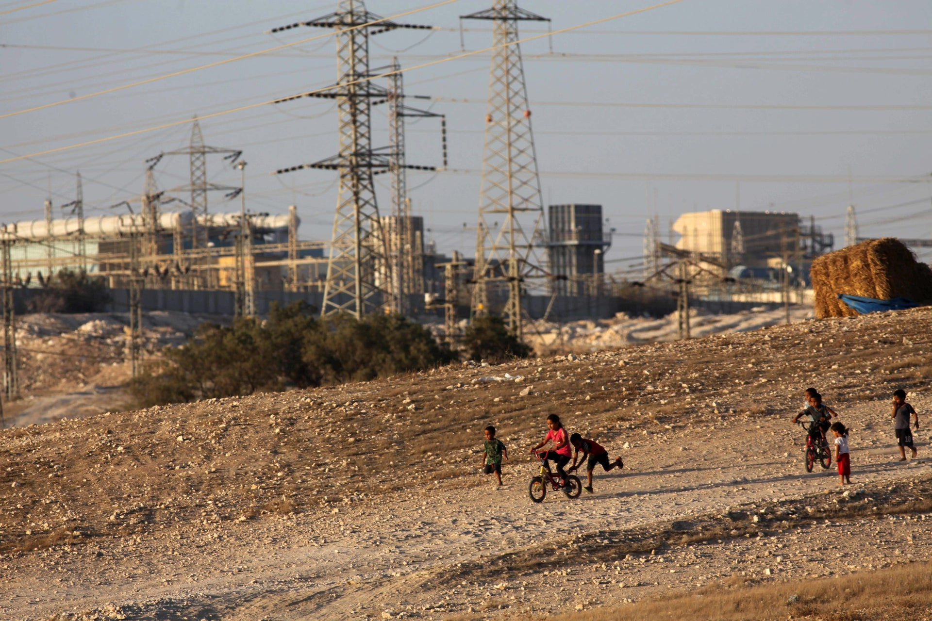Children from the village of Azazme play near the industrial zone of Ne'ot Hovav in southern Israel.