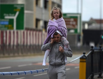 A man carries a young girl on his shoulders near Victoria station in Manchester, northwest England on May 23, 2017.