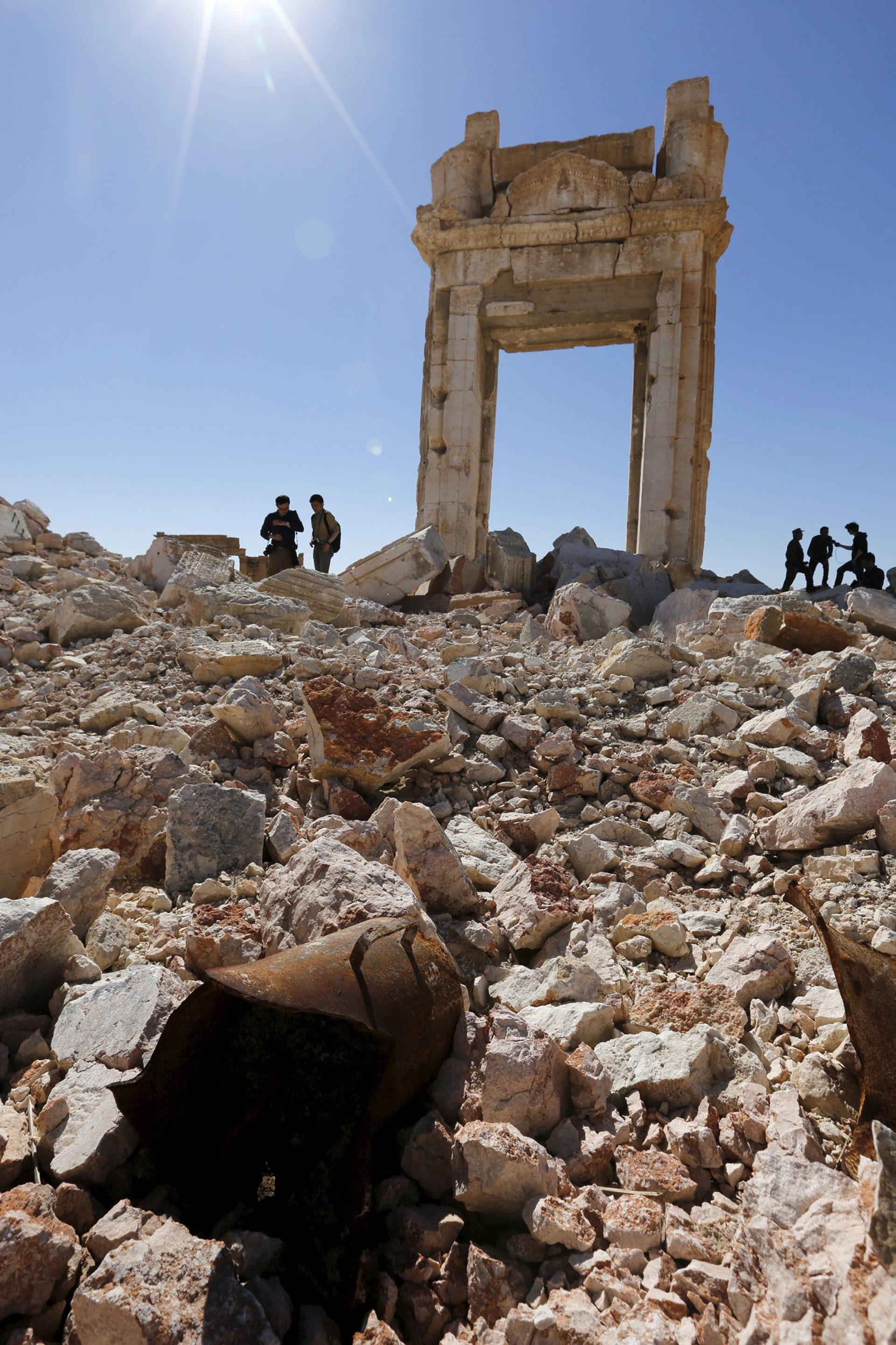 Journalists stand on ruins of theTemple of Bel in historic city of Palmyra, in Homs Governorate, Syria April 1, 2016.