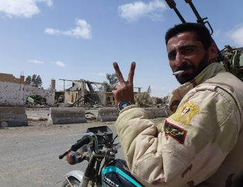 A member of the Syrian pro-government forces flashes the V-sign after re-capturing Palmyra from ISIS, Palmyra, Syria, March 27, 2016.