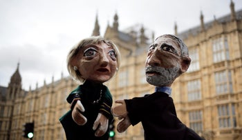 Two anti-Brexit activists pose with their hand-puppets depicting British Prime Minister and leader of the Conservative party Theresa May, left, and Britain's Labour party leader Jeremy Corbyn, during a protest, in front of the the Houses of Parliament on election day in London, Thursday, June 8, 2017.