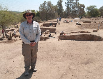 Prof. Aren Maier standing by the Gates of Gath. The professor is wearing hat, sunglasses and appropriate clothes for a dig. In the background we see the remains of walls and fortifications, and some of the excavators at work.