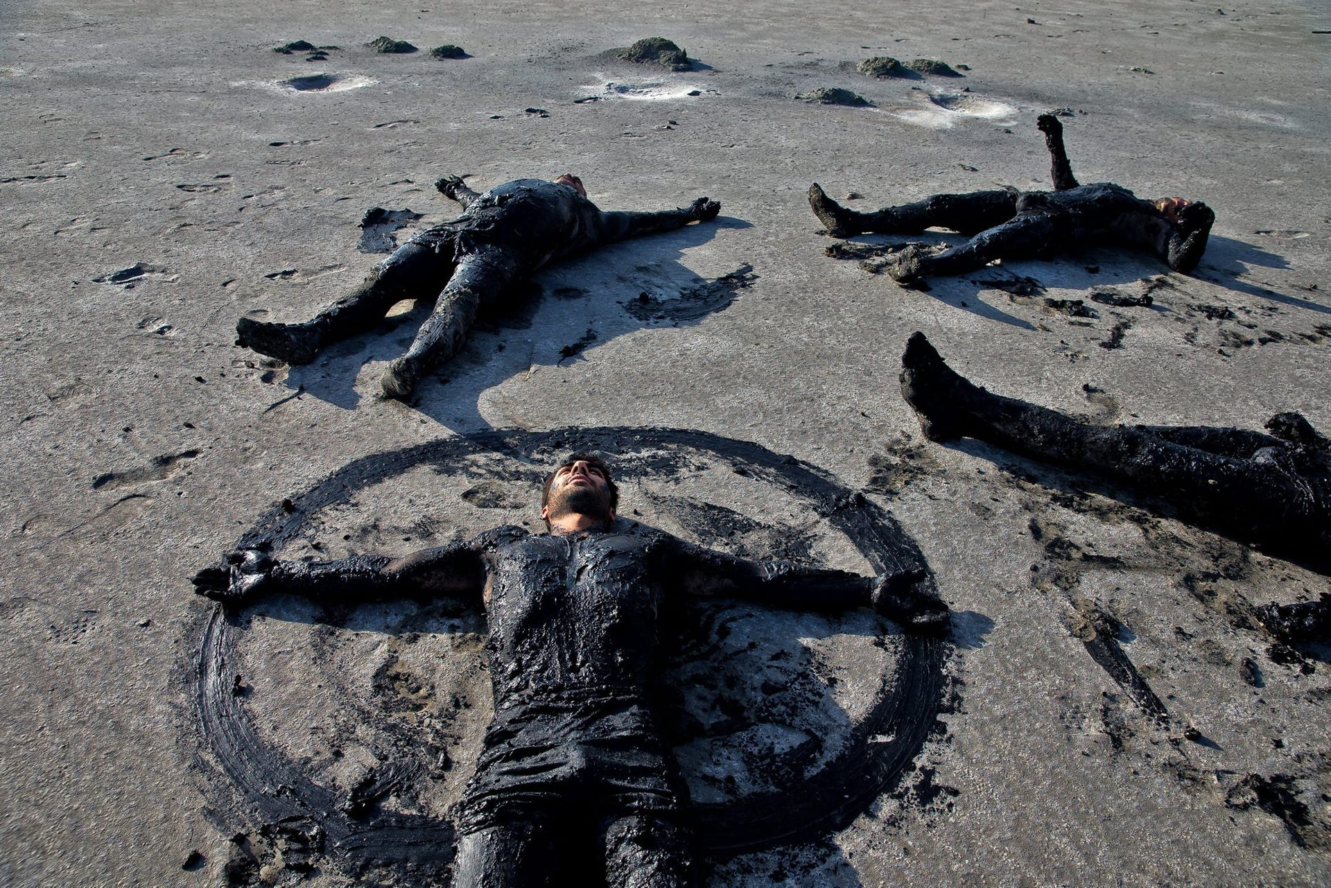 This picture taken on Saturday, Aug. 27, 2016, shows Iranians lying beside Urmia Lake with their bodies covered with mud near Urmia, northwestern Iran. Hopes for survival of Urmia salt lake have been revived after more rains boosted a government program aimed at preserving the almost dried up water body.