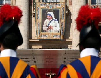 Swiss Guards stand in front of a tapestry depicting Mother Teresa of Calcutta before a mass, celebrated by Pope Francis, for her canonisation in Saint Peter's Square at the Vatican September 4, 2016.