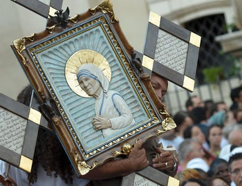 A man holds an icona of Mother Teresa of Kolkata as he arrives for the holy mass and Canonisation of the nun, on St. Peter square in the Vatican, on September 4, 2016. Mother Teresa, the celebrated nun whose work with the poor of Kolkata made her an instantly recognisable global figure, will be proclaimed a saint on September 4, 2016.  Pope Francis will preside over a solemn canonisation mass in the presence of 100,000 pilgrims and with a giant haloed portrait of Teresa smiling down from St Peter's Basilica.