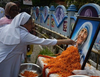 Indian Christians and nuns gather to pay their respects by a portrait of Mother Teresa in Siliguri on September 4, 2016. Pope Francis on September 4 proclaimed Mother Teresa a saint, hailing her work with the destitute of Kolkata as a beacon for mankind and testimony of God's compassion for the poor. The revered nun's elevation to Roman Catholicism's celestial pantheon came in a canonisation mass in St Peter's square presided over by Pope Francis in the presence of 100,000 pilgrims.
