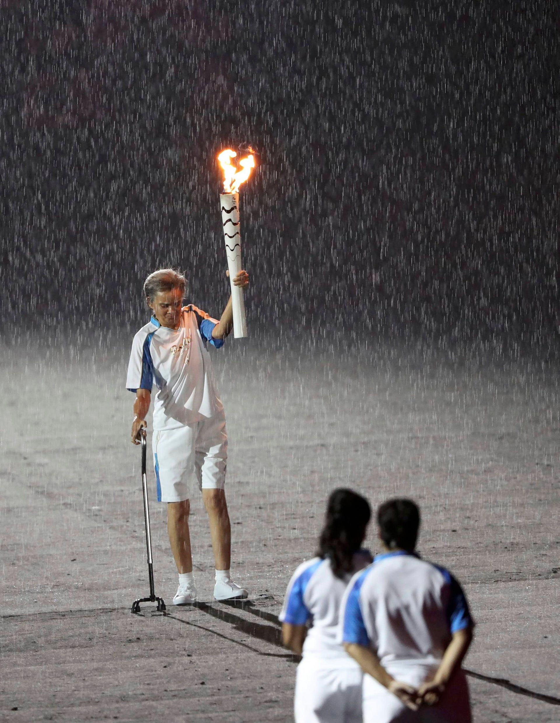 2016 Rio Paralympics - Opening ceremony - Maracana - Rio de Janeiro, Brazil - 07/09/2016. Brazilian Paralympic runner Marcia Malsar continues carrying the torch after falling as rain falls during the opening ceremony.