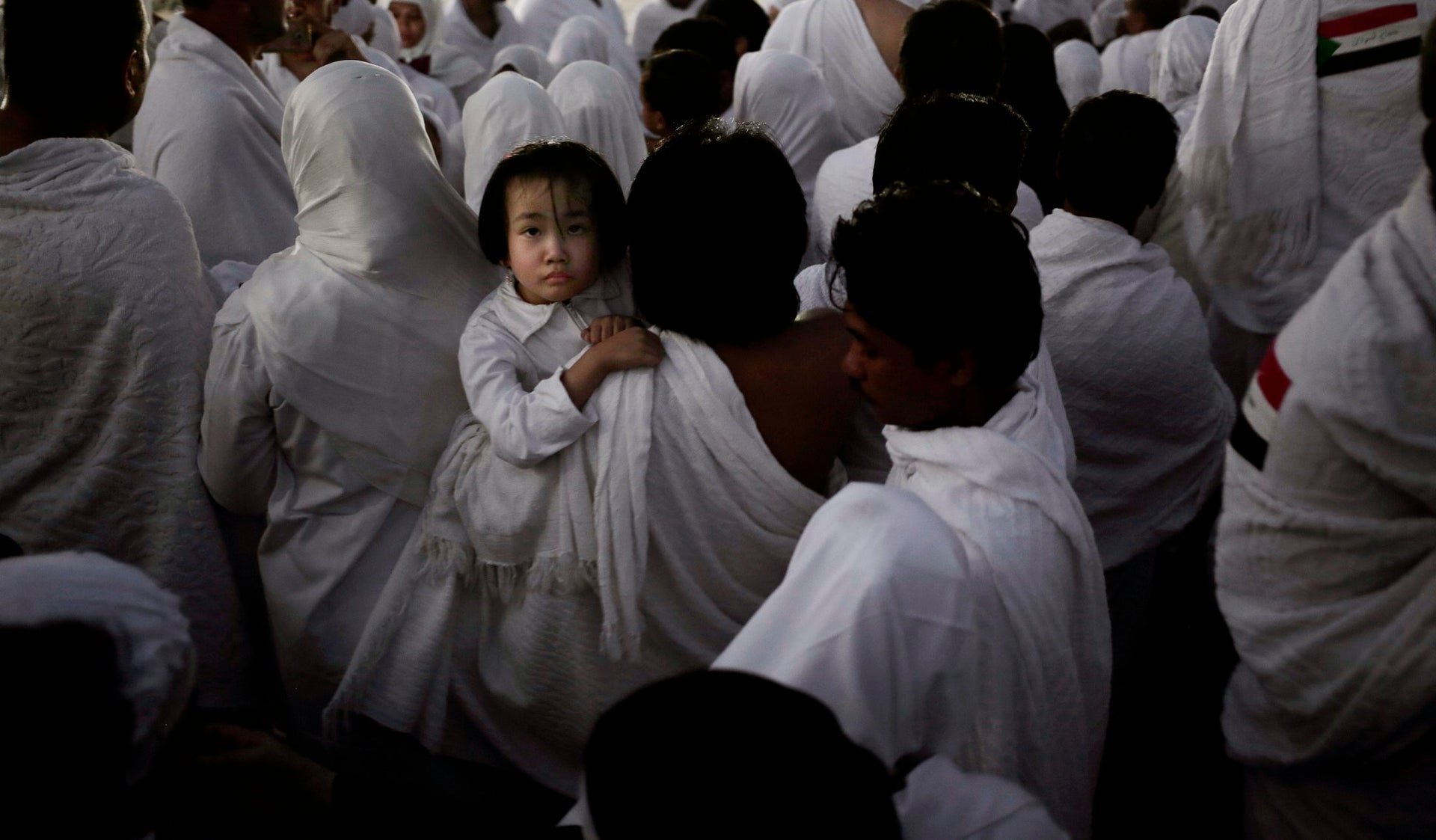 An Indonesian father carries his daughter through the crowd after reaching the top of a rocky hill known as Mountain of Mercy, on the Plain of Arafat, during the annual hajj pilgrimage, ahead of sunrise near the holy city of Mecca, Saudi Arabia, Sunday, Sept. 11, 2016. Mount Arafat, marked by a white pillar, is where Islam's Prophet Muhammad is believed to have delivered his last sermon to tens of thousands of followers some 1,400 years ago, calling on Muslims to unite.