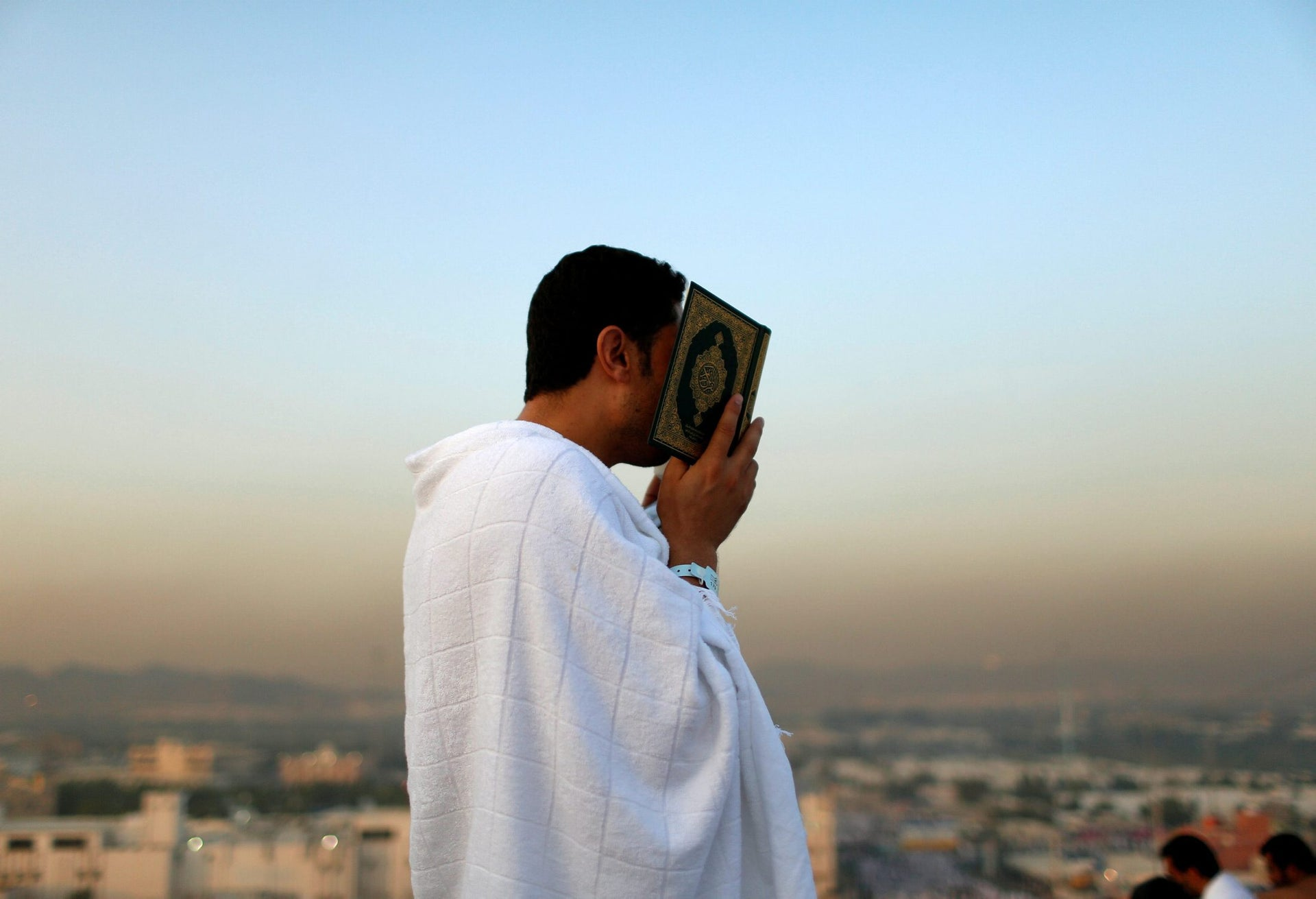 A Muslim pilgrim holds a copy of the Koran as he prays on Mount Mercy on the plains of Arafat during the annual haj pilgrimage, outside the holy city of Mecca, Saudi Arabia September 11, 2016.