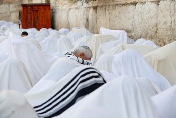 Jewish worshippers cover themselves in prayer shawls as they recite the priestly blessing at the Western Wall in Jerusalem's Old City during the Jewish holiday of Sukkot October 19, 2016.