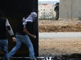 A Palestinian protester takes cover as he throws stones towards Israeli troops in the West Bank village of Bilin, near Ramallah, February 17, 2017.